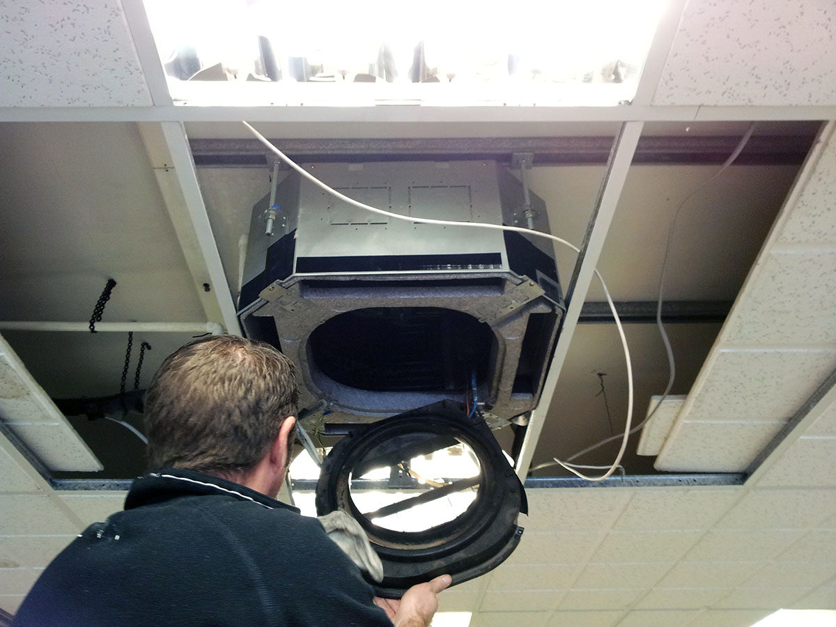 Torr Engineering engineer Garry Ornsby cleaning an air conditioning unit evaporator.